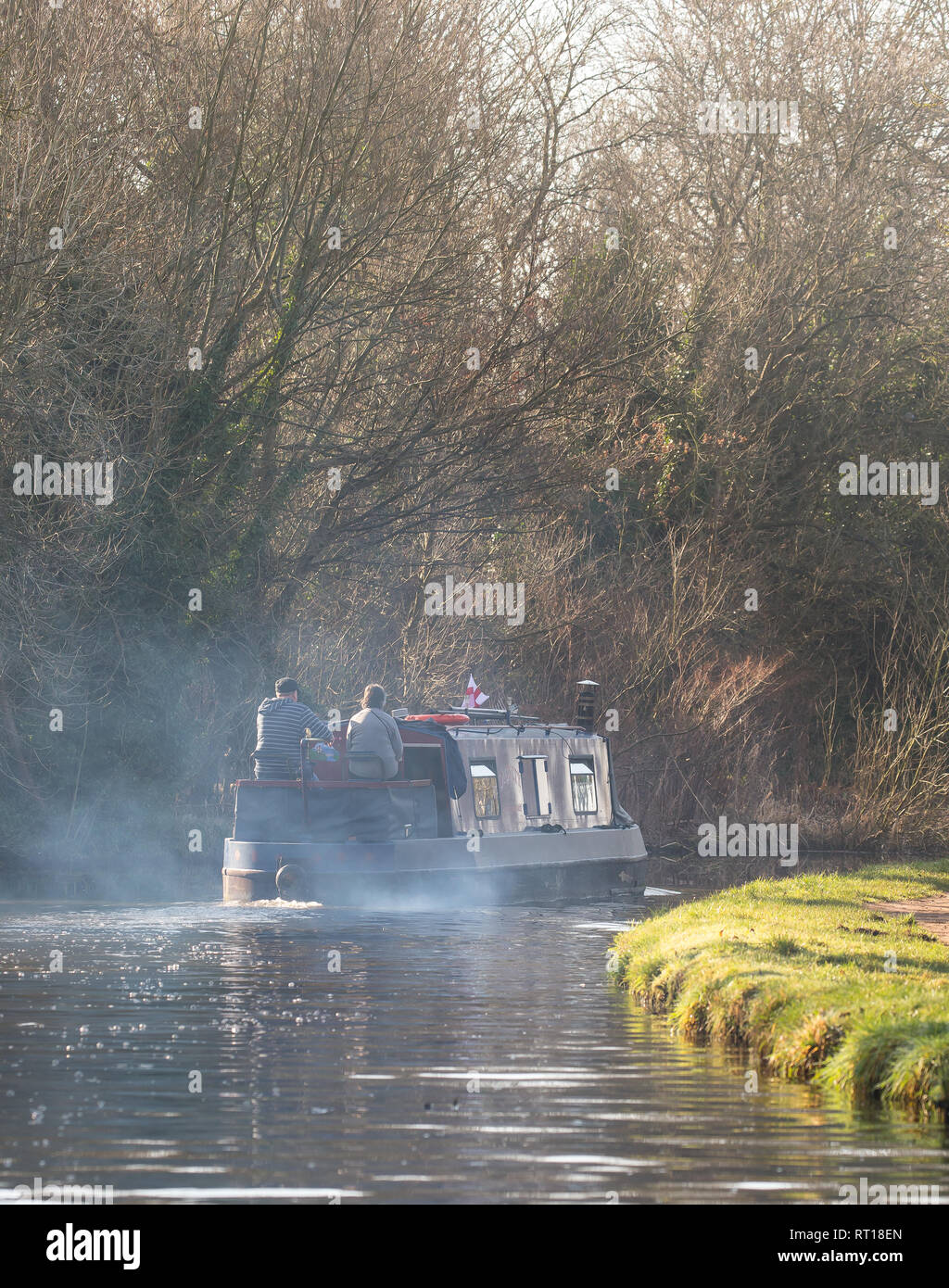 Kidderminster, UK. 27th February, 2019. UK weather: beautiful sunshine in Worcestershire as temperatures head towards 15 degrees Celsius for the day. No winter coats or gloves are needed, just jumpers, as these two travellers enjoy the best of what Britain can offer, aboard their canal boat, on our inland waterways on this unusally warm February day. Credit Lee Hudson/Alamy Live News - Stock Image