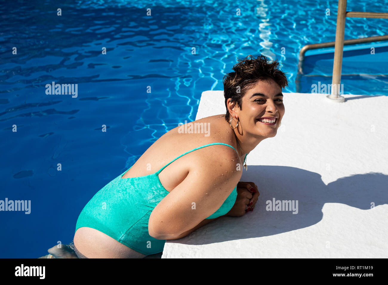 Portrait of plump young woman leaning at poolside - Stock Image