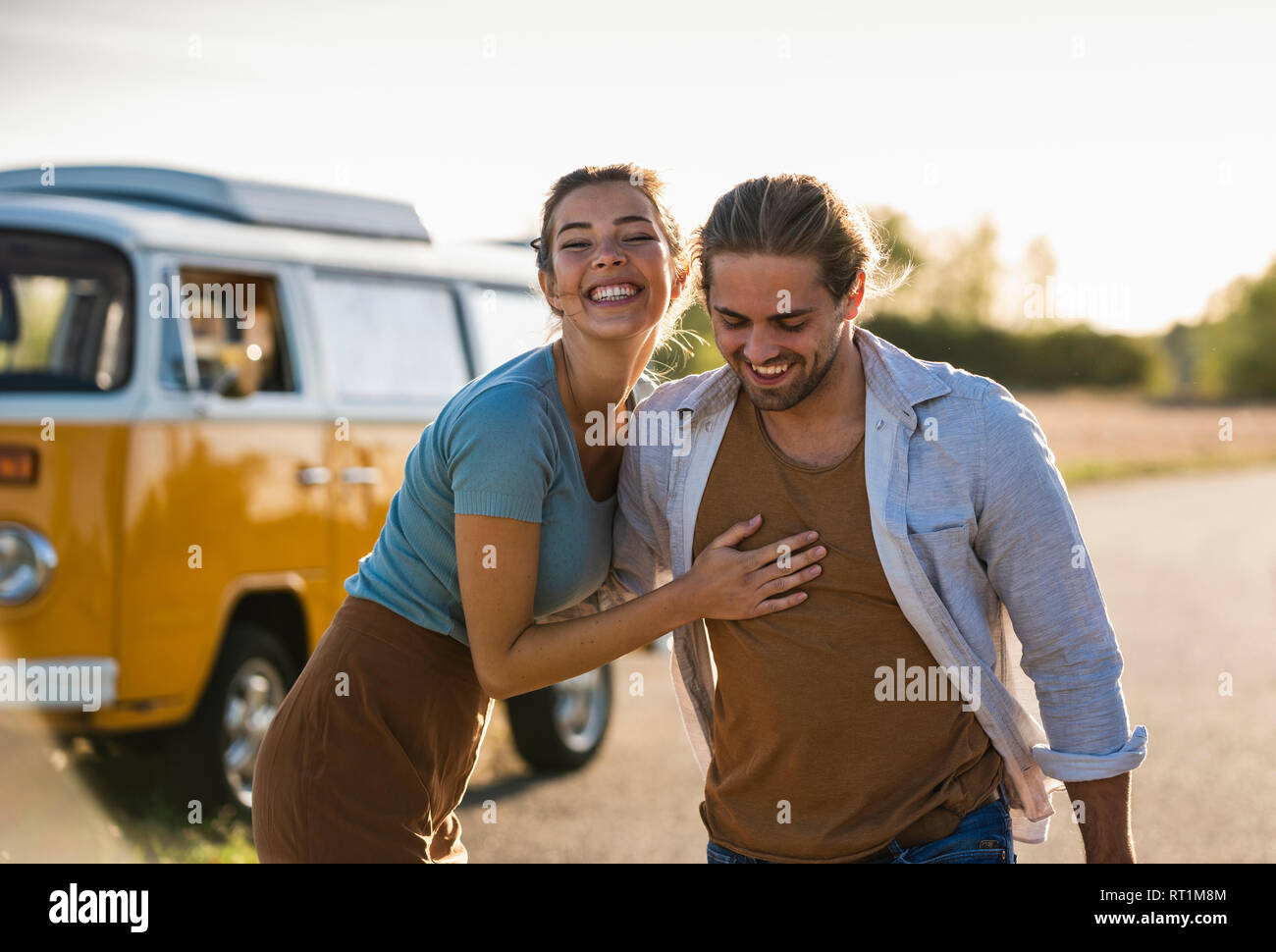 Happy couple doing a road trip with a camper, embracing on the road Stock Photo