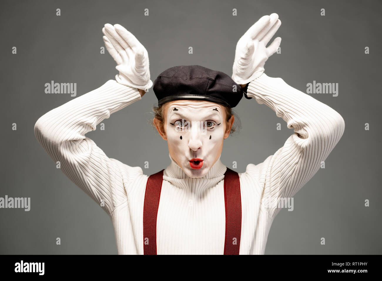 Portrait of a pantomime actor with white facial makeup posing with expressive emotions on the grey background indoors - Stock Image