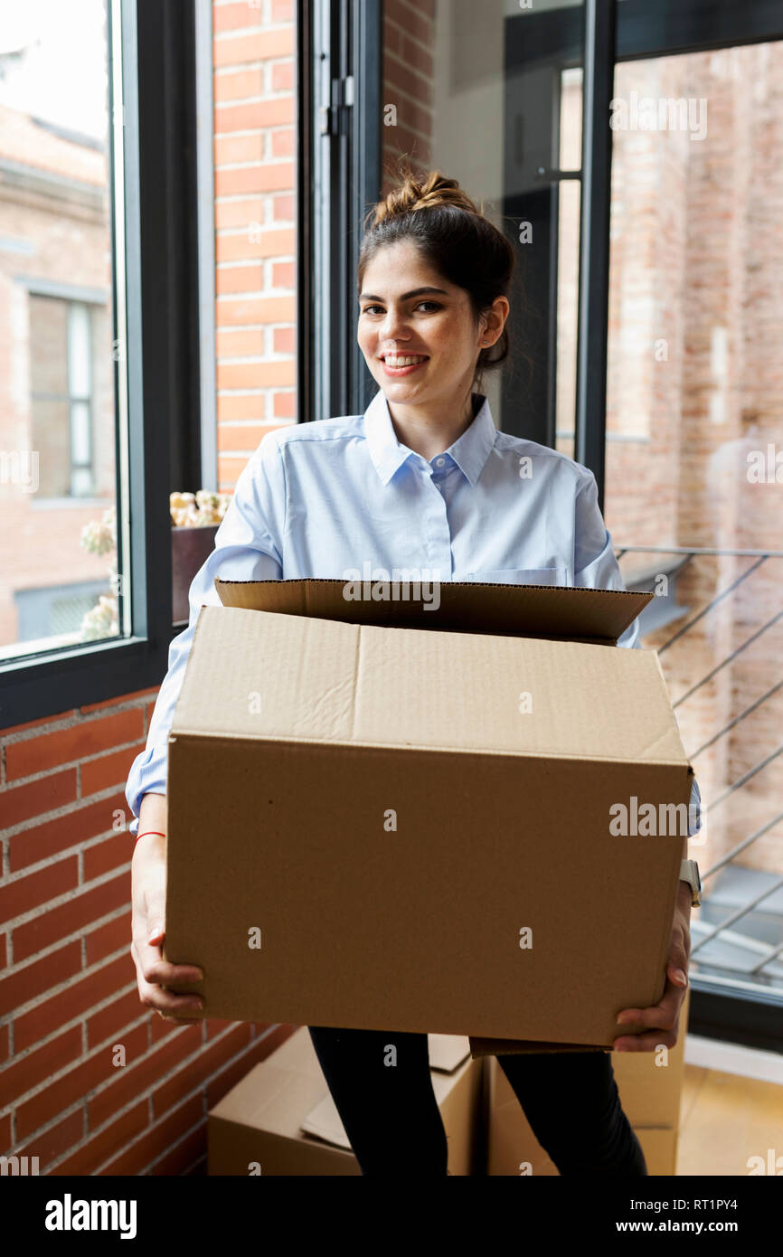 Portrait of smiling young woman carrying cardboard box in new apartment at the window - Stock Image