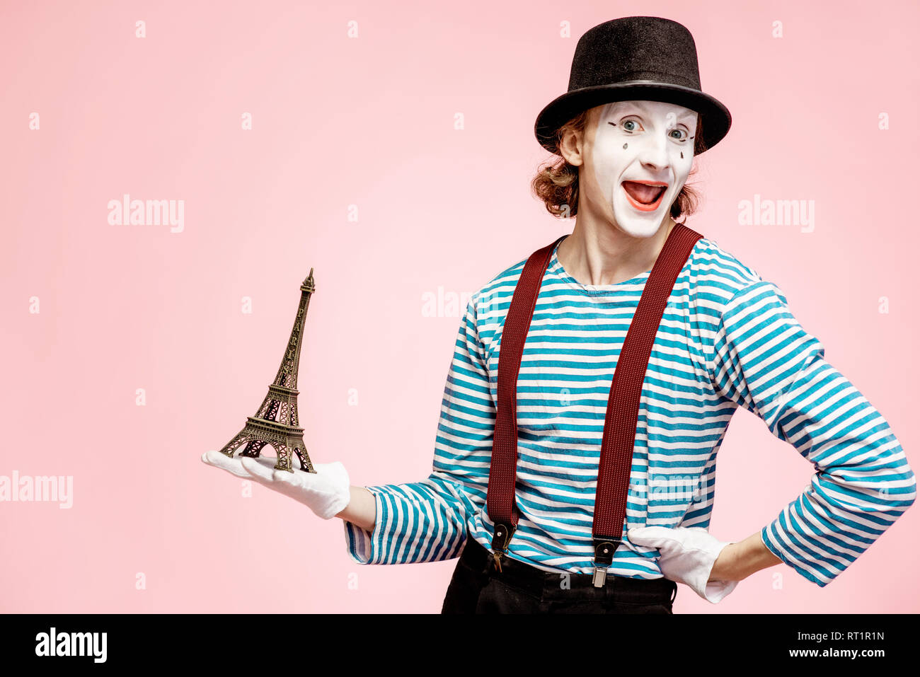 Pantomime with white facial makeup posing with Eiffel tower on the pink background. French mime concept - Stock Image