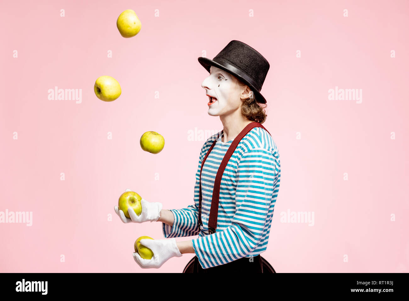 Pantomime with white facial makeup juggling with apples on the pink background in the studio - Stock Image