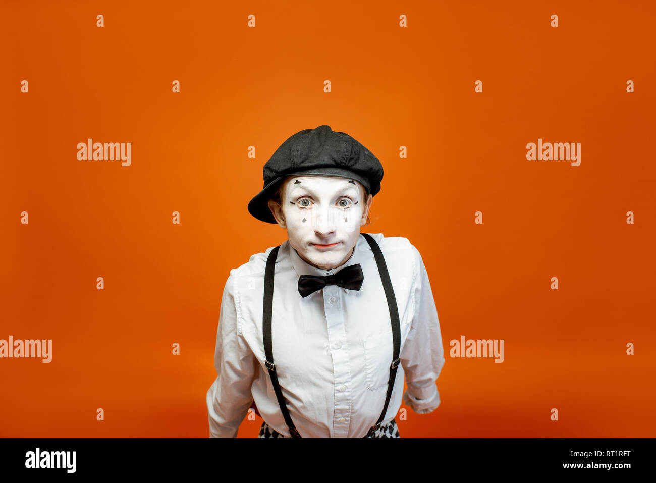 Portrait of an actor as a pantomime with white facial makeup showing expressive emotions on the orange background in the studio - Stock Image