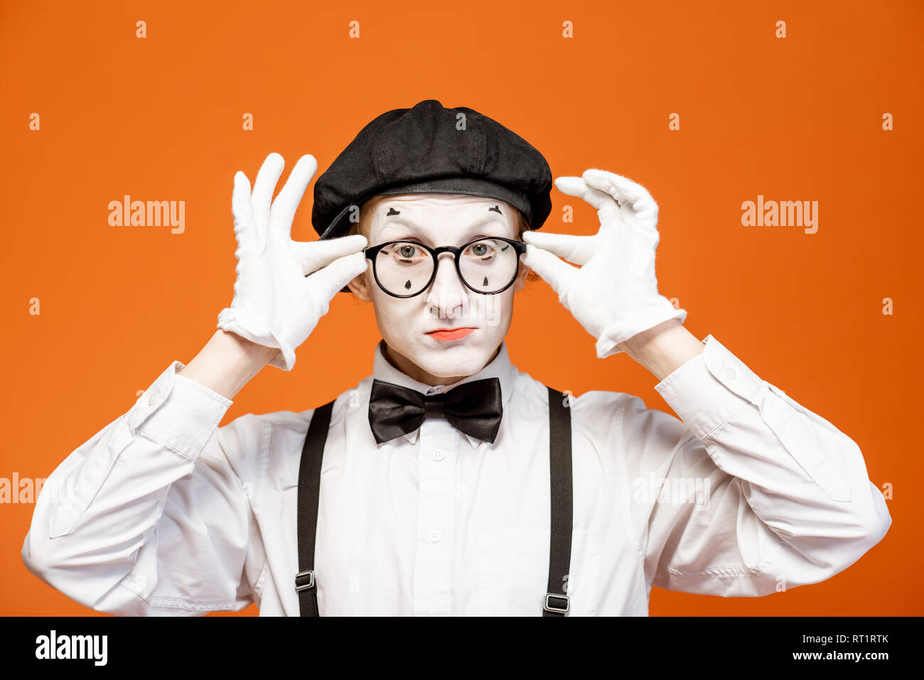Portrait of a pantomime with white facial makeup in eyeglasses showing expressive emotions on the orange background - Stock Image