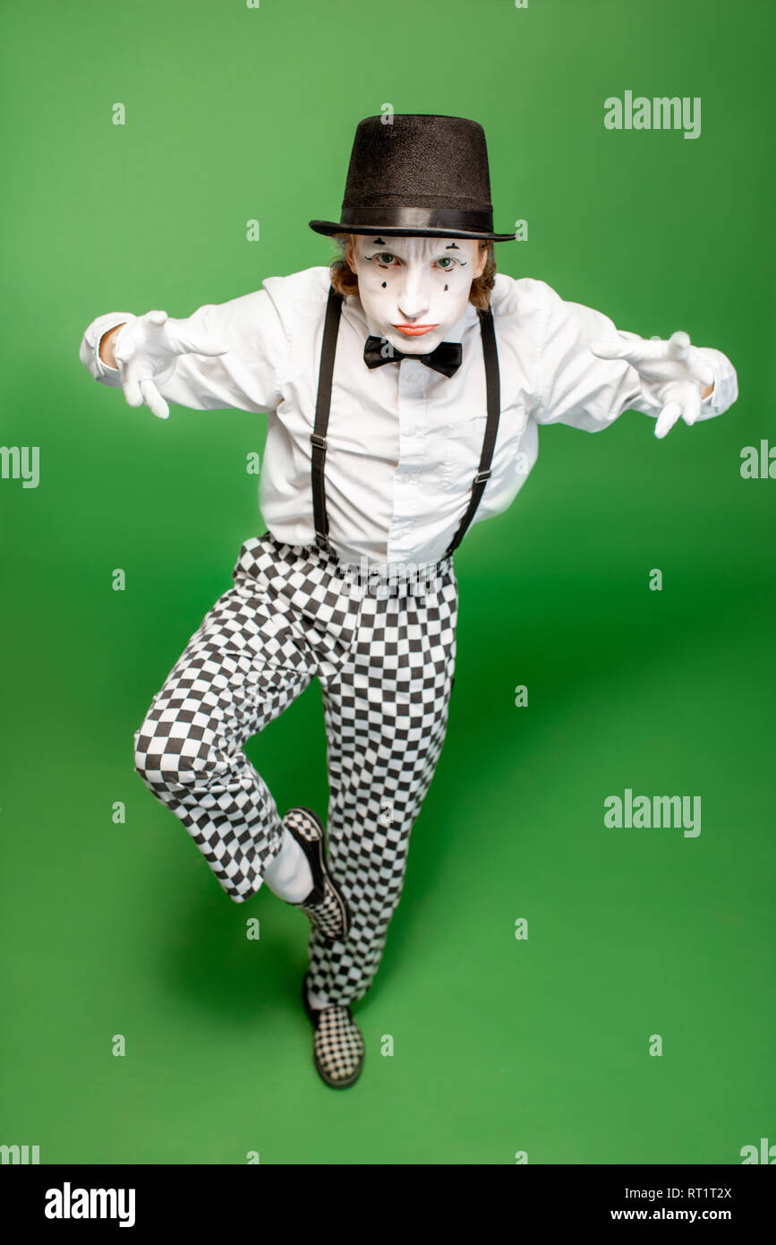 Full body portrait of an actor as a pantomime posing with expressive emotions isolated on the green background - Stock Image