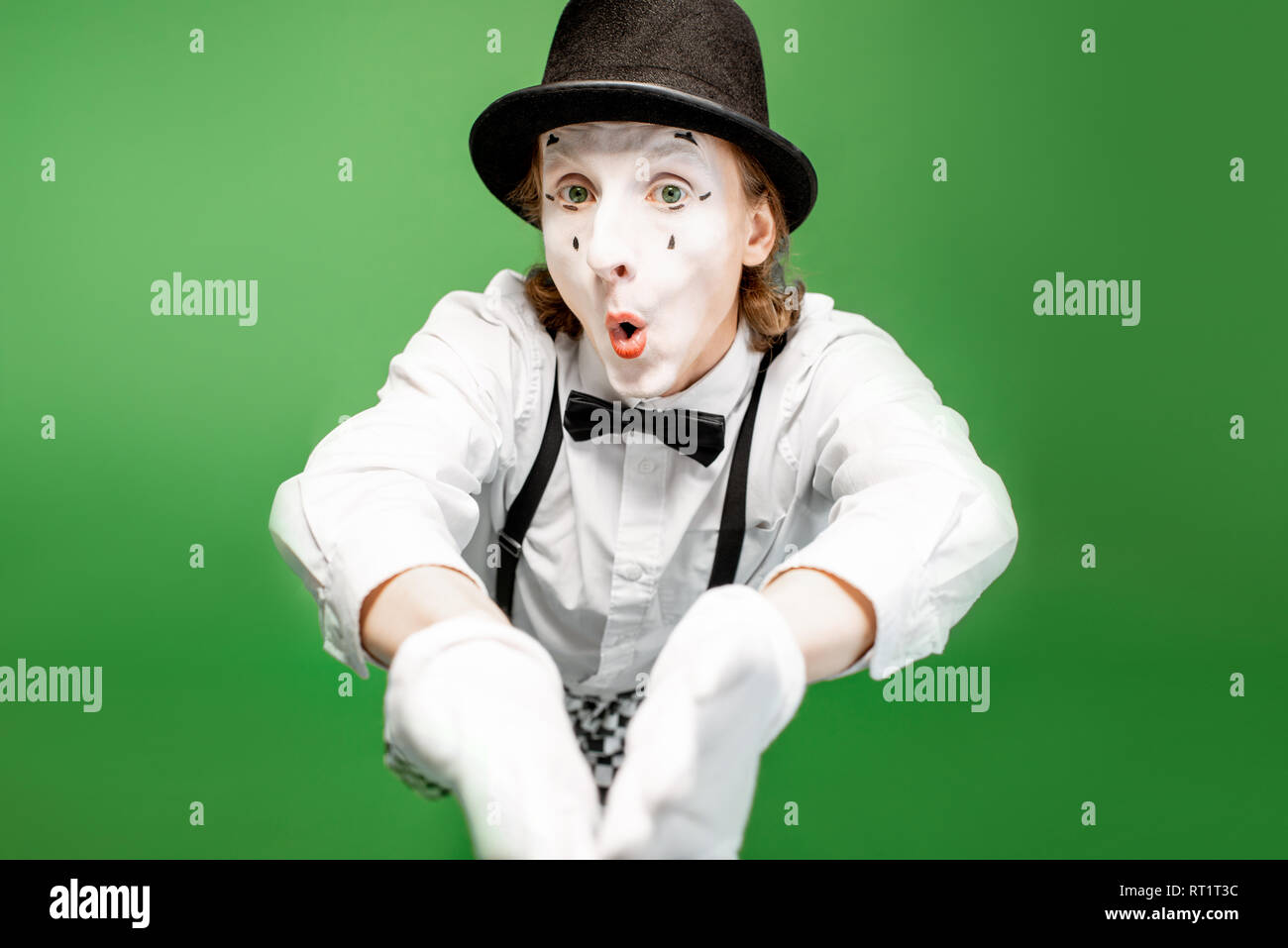 Portrait of an actor as a pantomime with white facial makeup posing with expressive emotions isolated on the green background - Stock Image