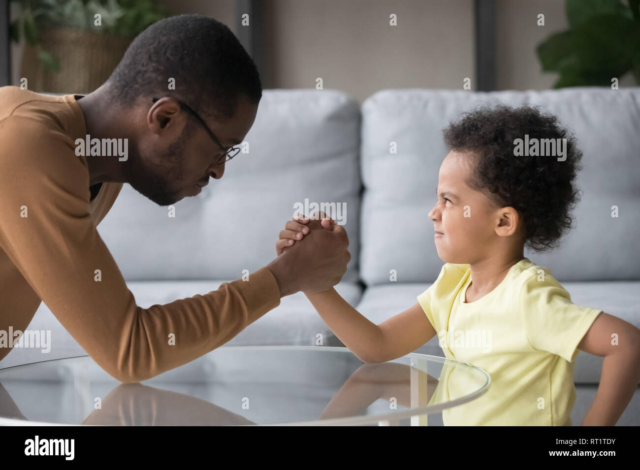 African dad and kid son with funny angry faces armwrestling Stock Photo