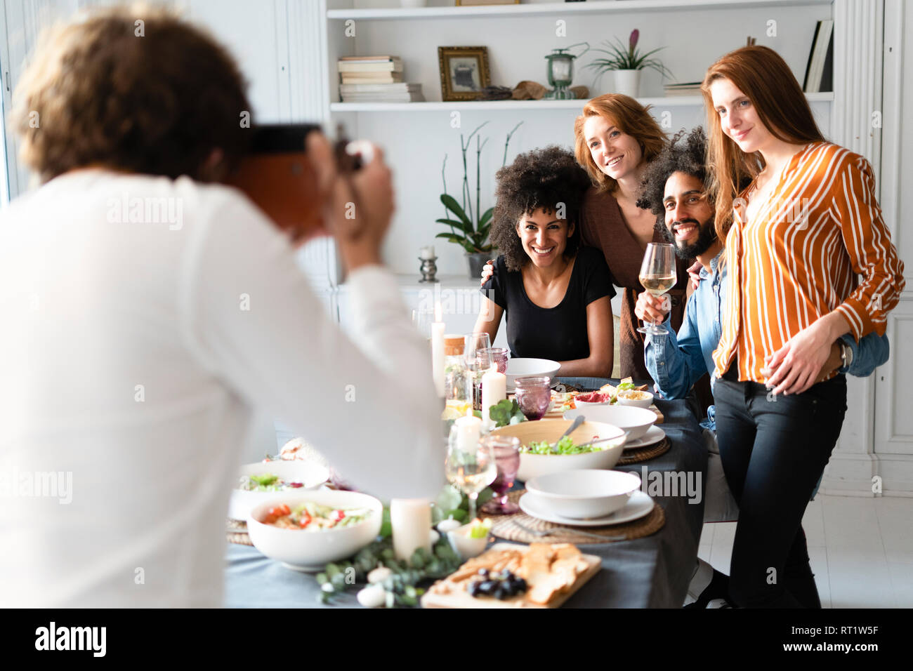 Friends taking a group picture as memory of a dinner party - Stock Image
