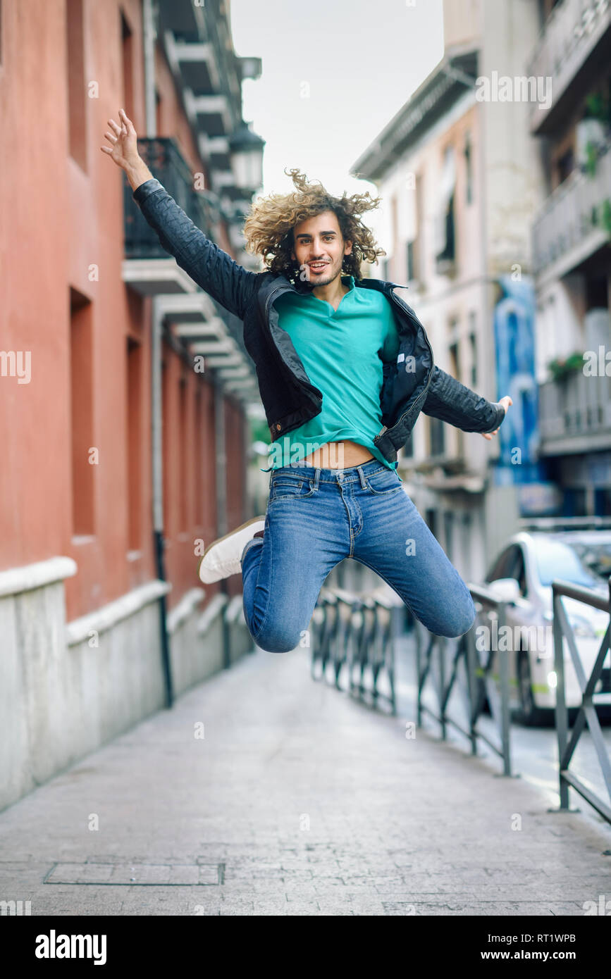 Portrait of smiling young man jumping in the air outdoors - Stock Image