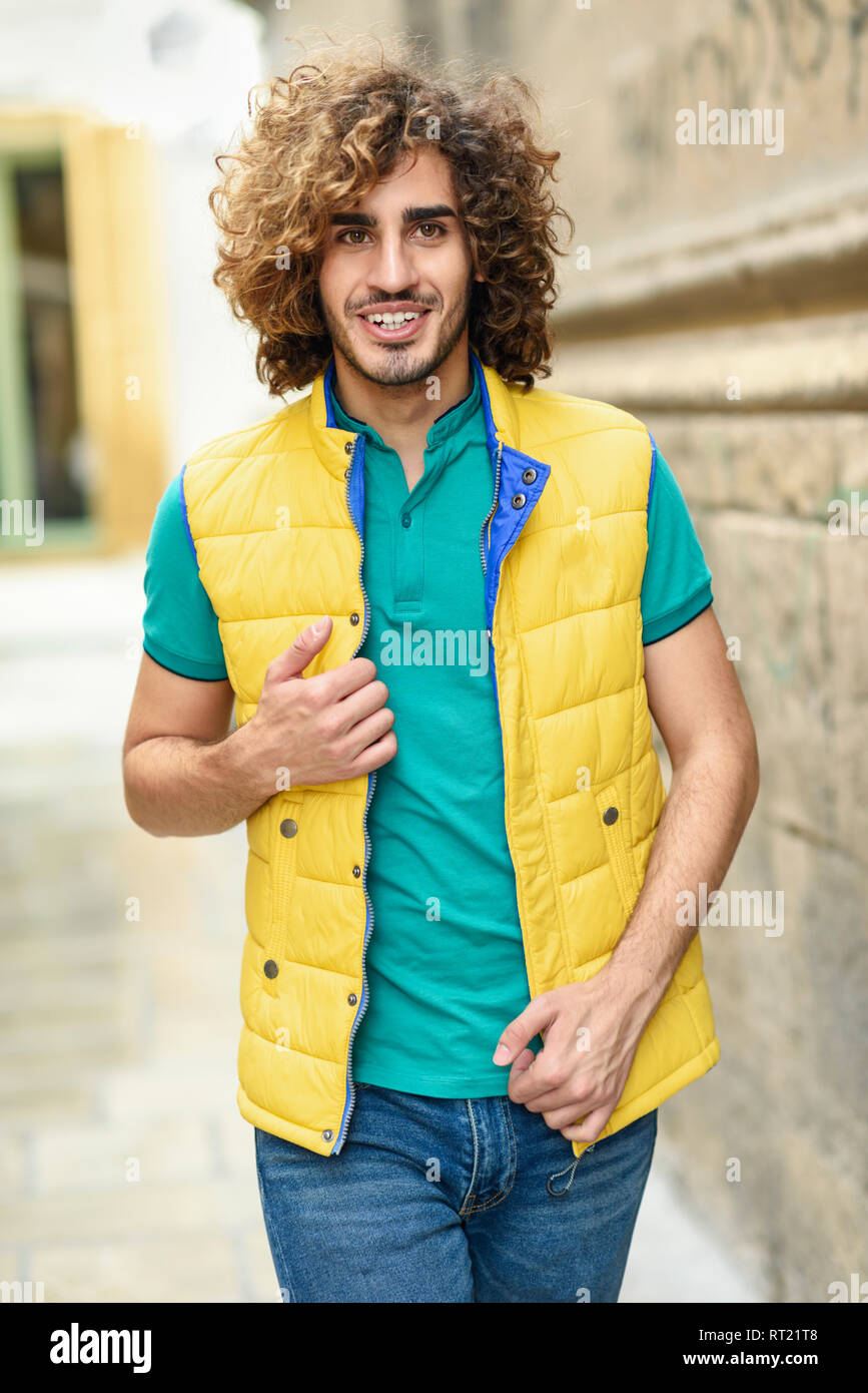 Portrait of smiling young man with curly hair wearing yellow waistcoat outdoors - Stock Image