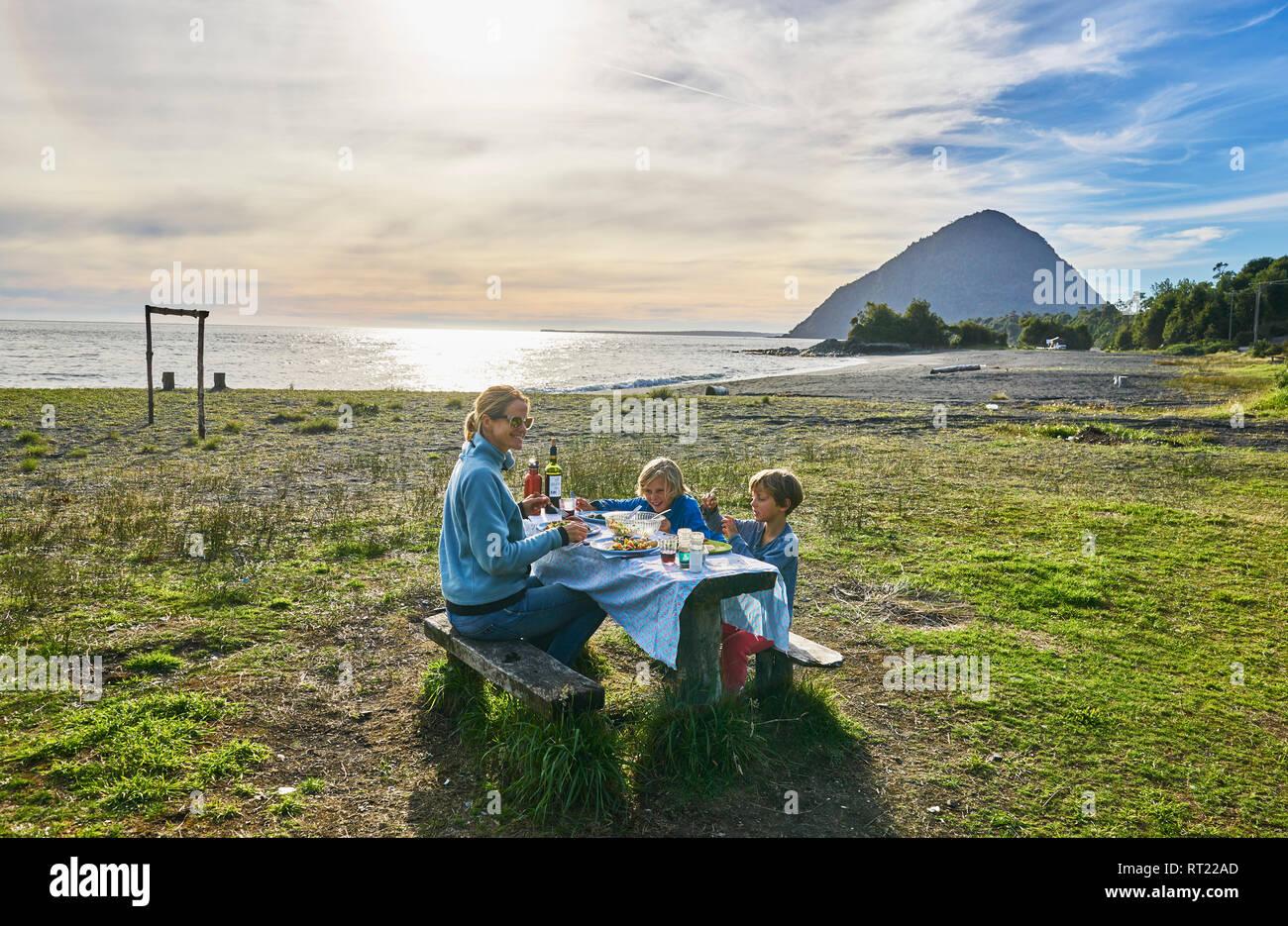 Chile, Chaiten, Carretera Austral, family having picnic at the beach - Stock Image