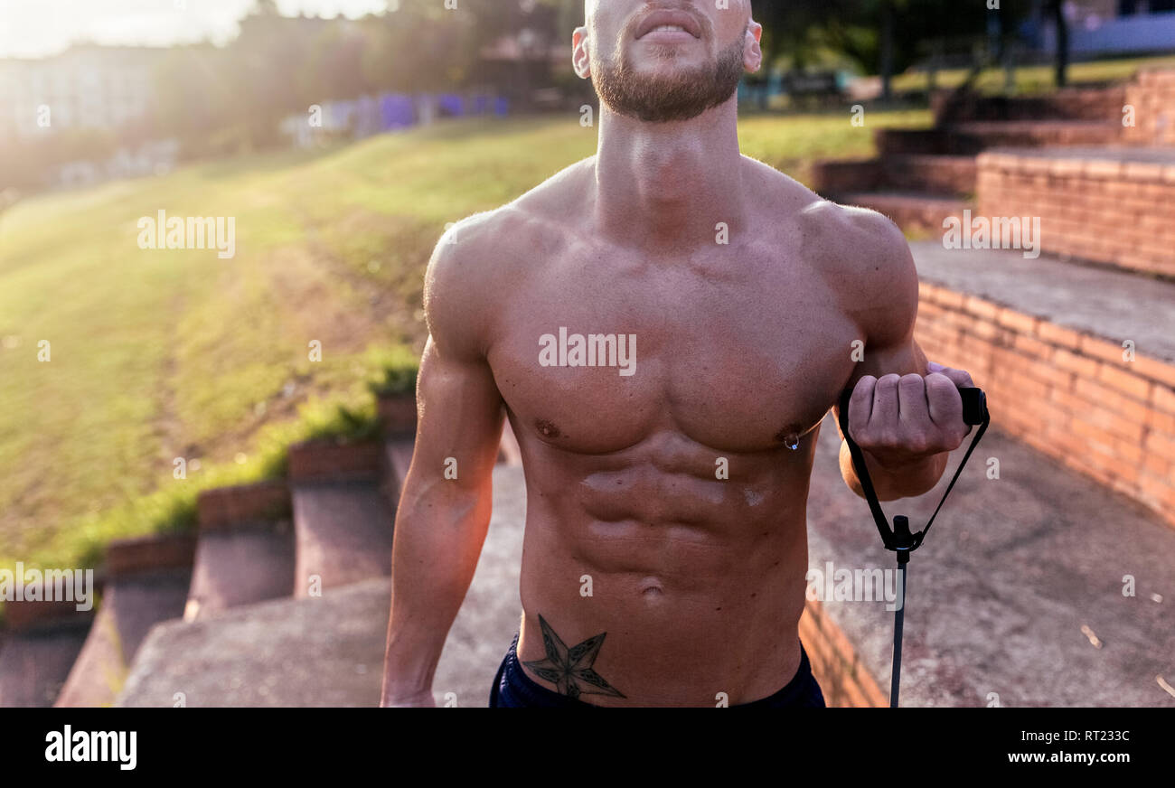 Mid-section of barechested muscular man exercising with expander outdoors - Stock Image
