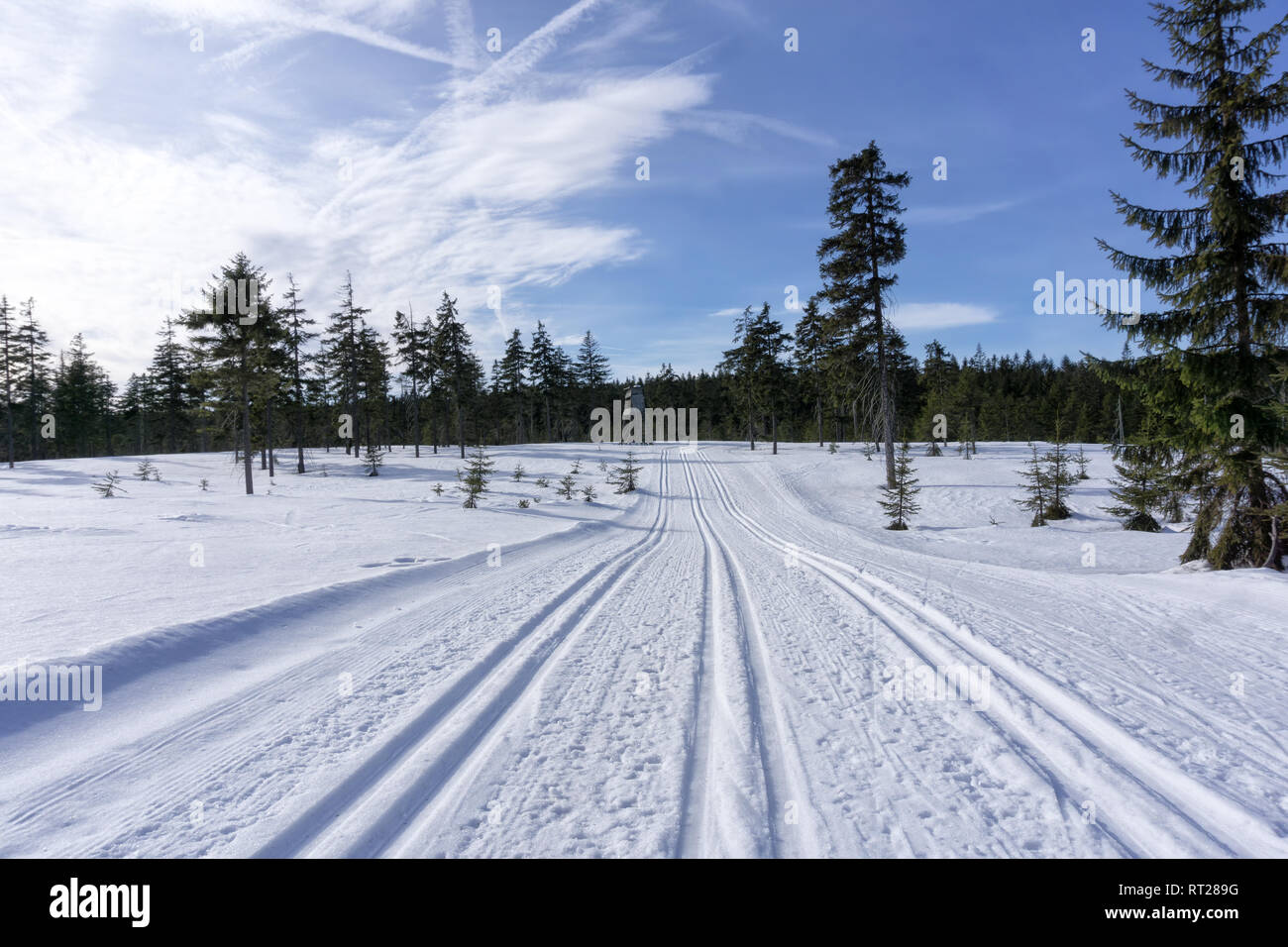 Winter mountain landscape with groomed ski track and blue sky in sunny day. Jizera Mountains, surroundings of Jakuszyce, Poland. - Stock Image