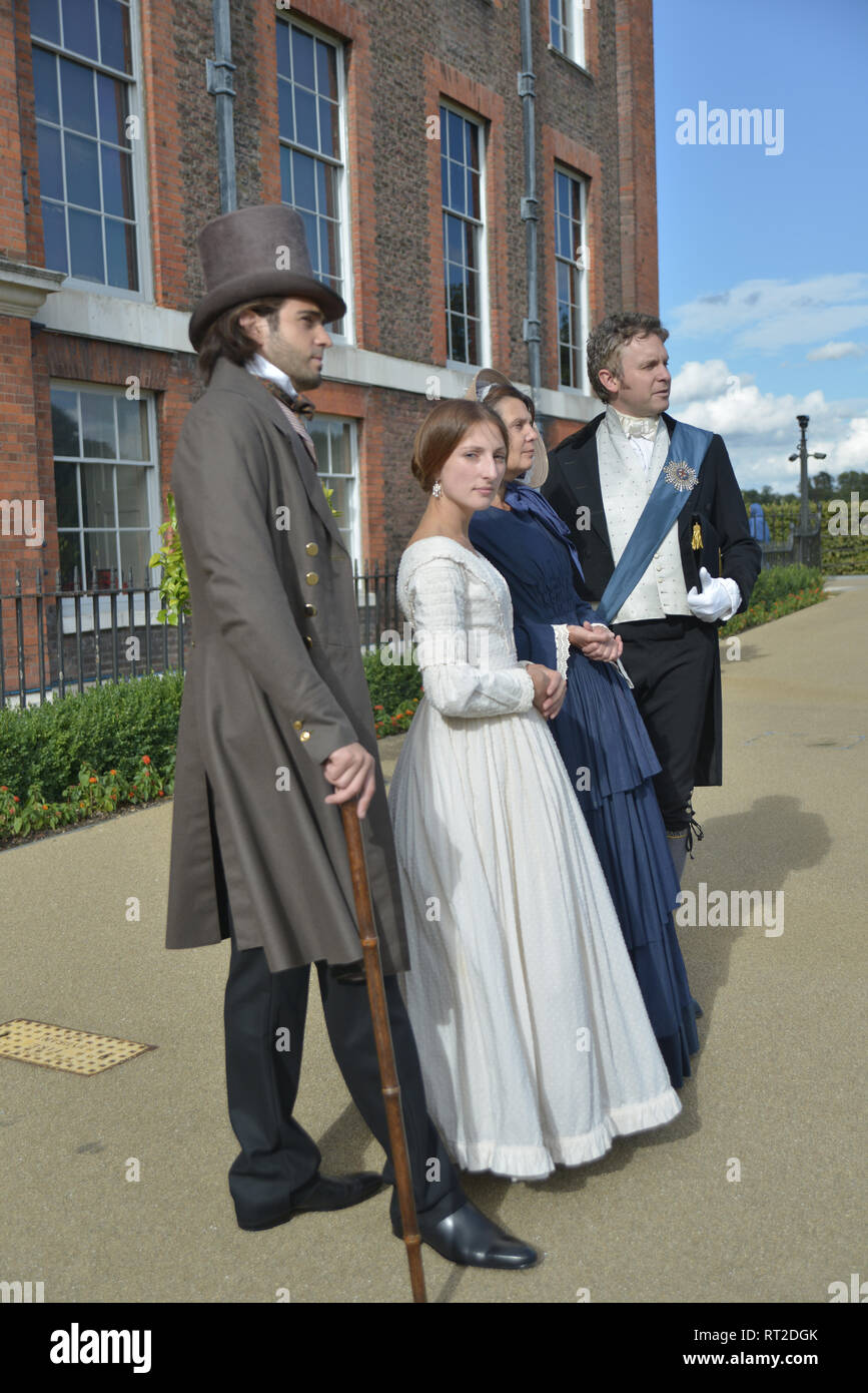 Queen Victoria, 2 gentlemen and her Baroness Lehzen stand in front of Kensington Palace and look at the grounds. - Stock Image
