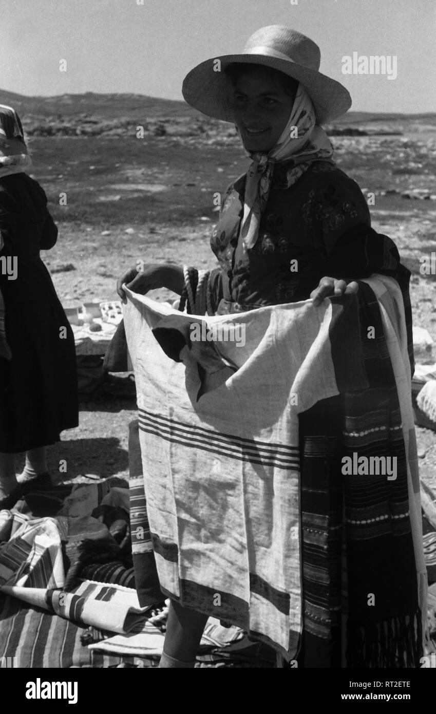 Griechenland, Greece - Eine Frau bietet handgeschneiderte Hemden als Souvenir an Touristen auf Delos, Griechenland, 1950er Jahre, an. A woman offering handmade shirts as a souvenir to tourist on the island of Delos, Greece, 1950s. - Stock Image