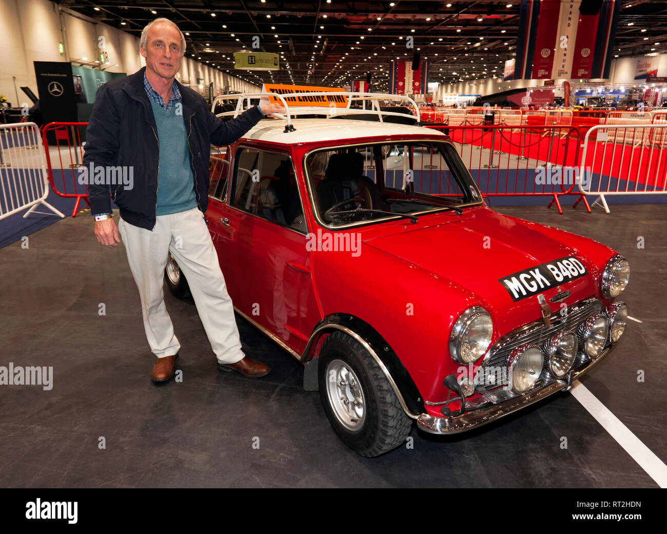 Alan Willcox posing by his twin-engine, Austin Mini Cooper S, at the 2019 London Classic Car Show. - Stock Image
