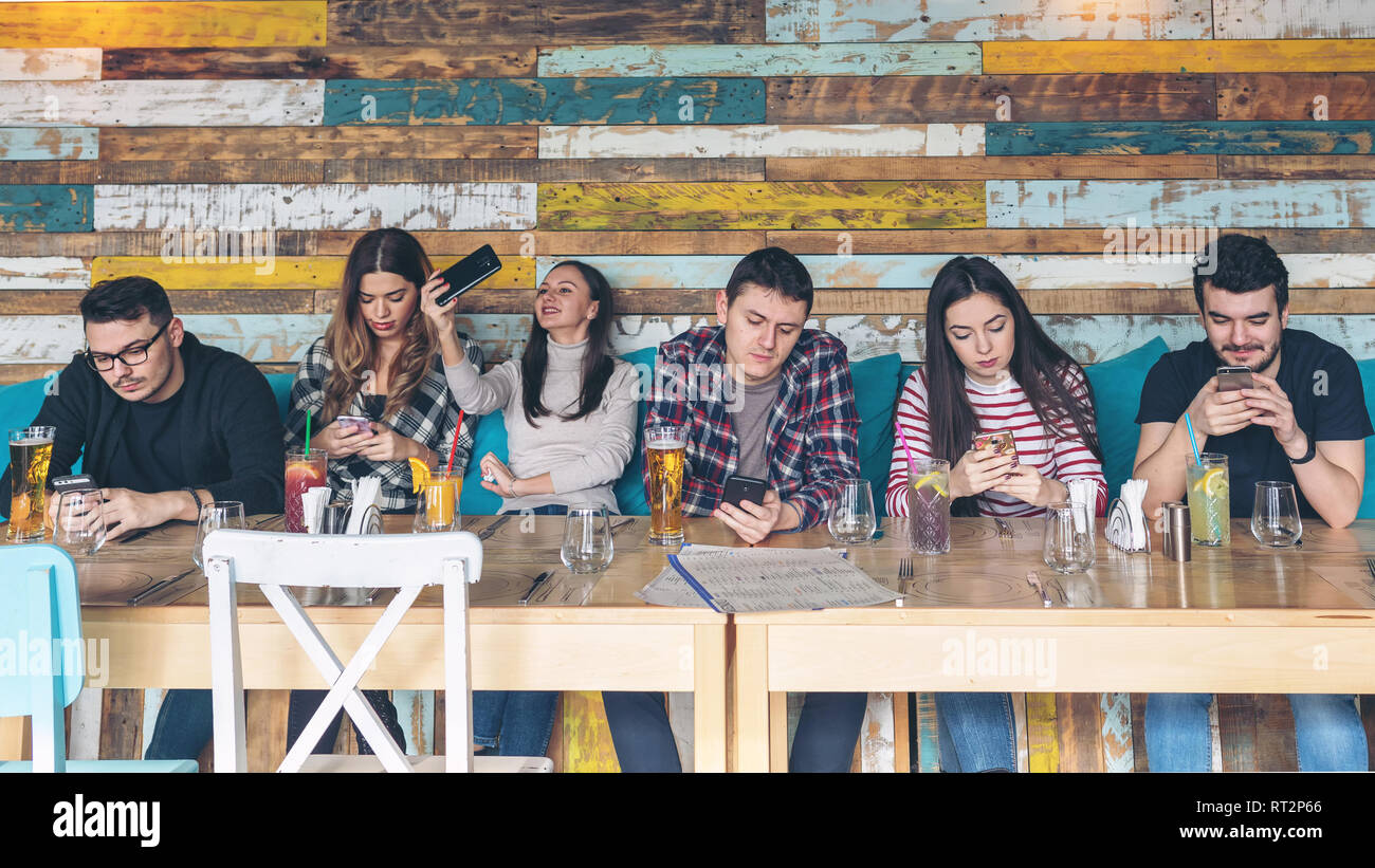 Group of friends using smartphone at rustic restaurant - Young hipster people addicted by mobile phone on social network community - Technology concep - Stock Image
