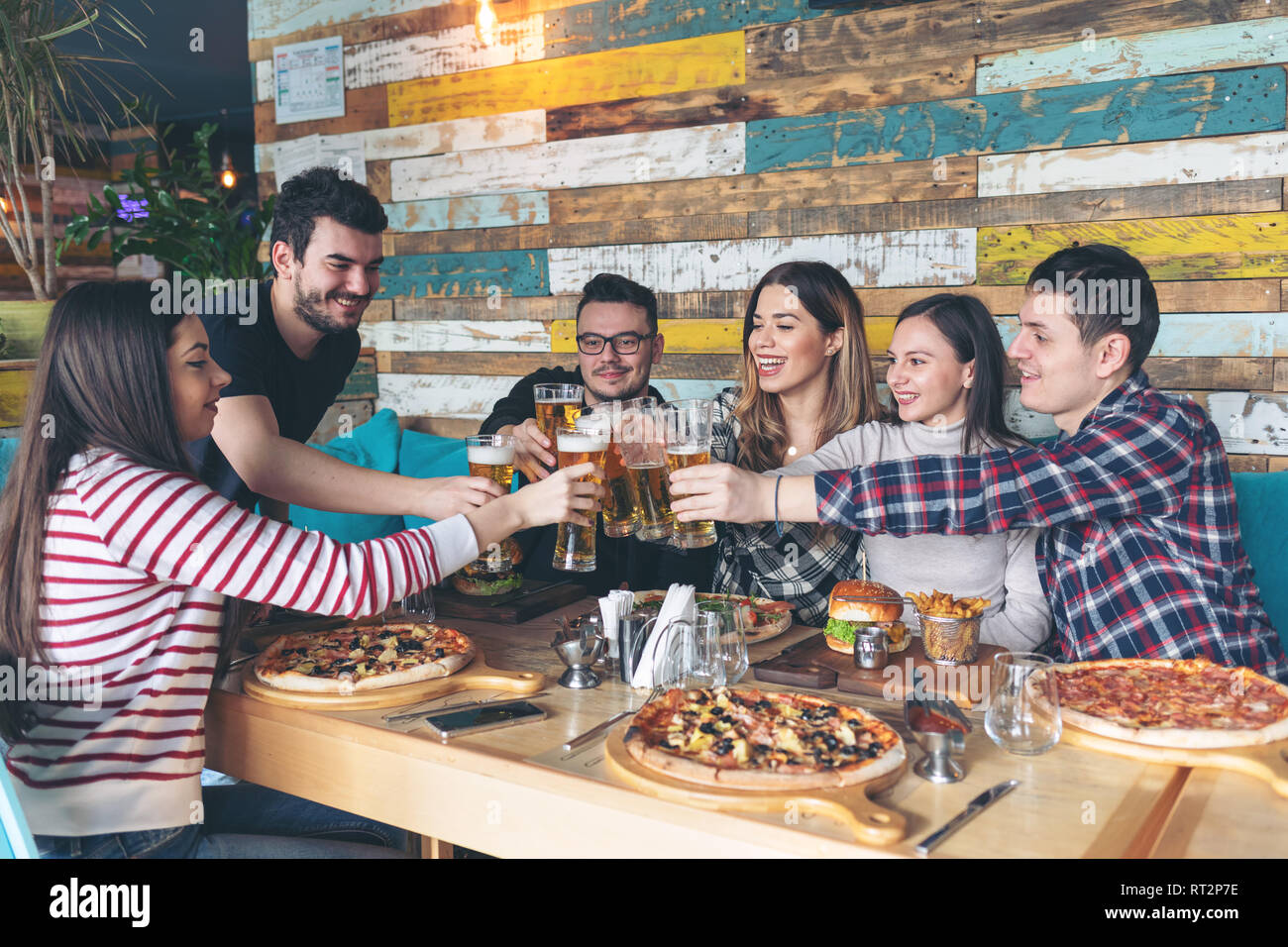 Happy young friends celebrating with pizza and drinking beer at bar restaurant - Friendship concept with young people enjoying time together and havin - Stock Image