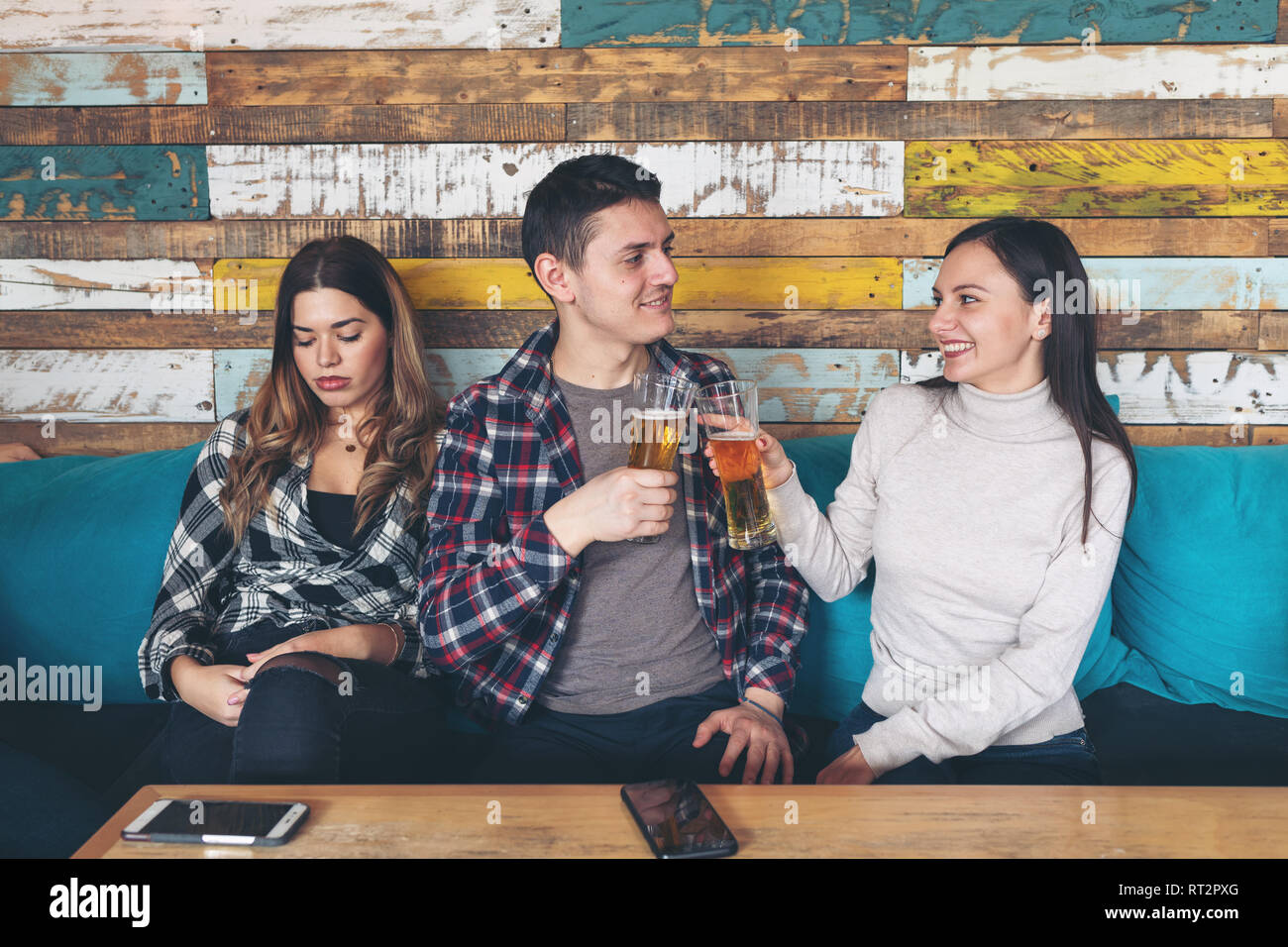 Happy young girl drinking beer with young man and socialise ignoring other jealous sad woman sitting next to them at rustic bar restaurant. Love and j - Stock Image
