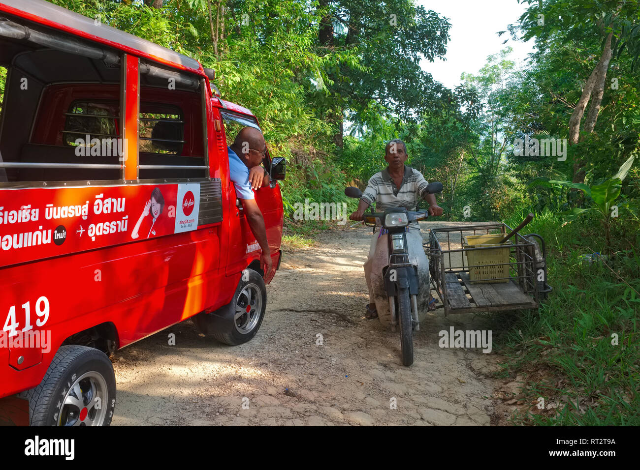 On a jungle path on Phuket island, Thailand, the driver of a tuk-tuk or songthaew (local small bus or van), asks a local rubber tapper for directions - Stock Image