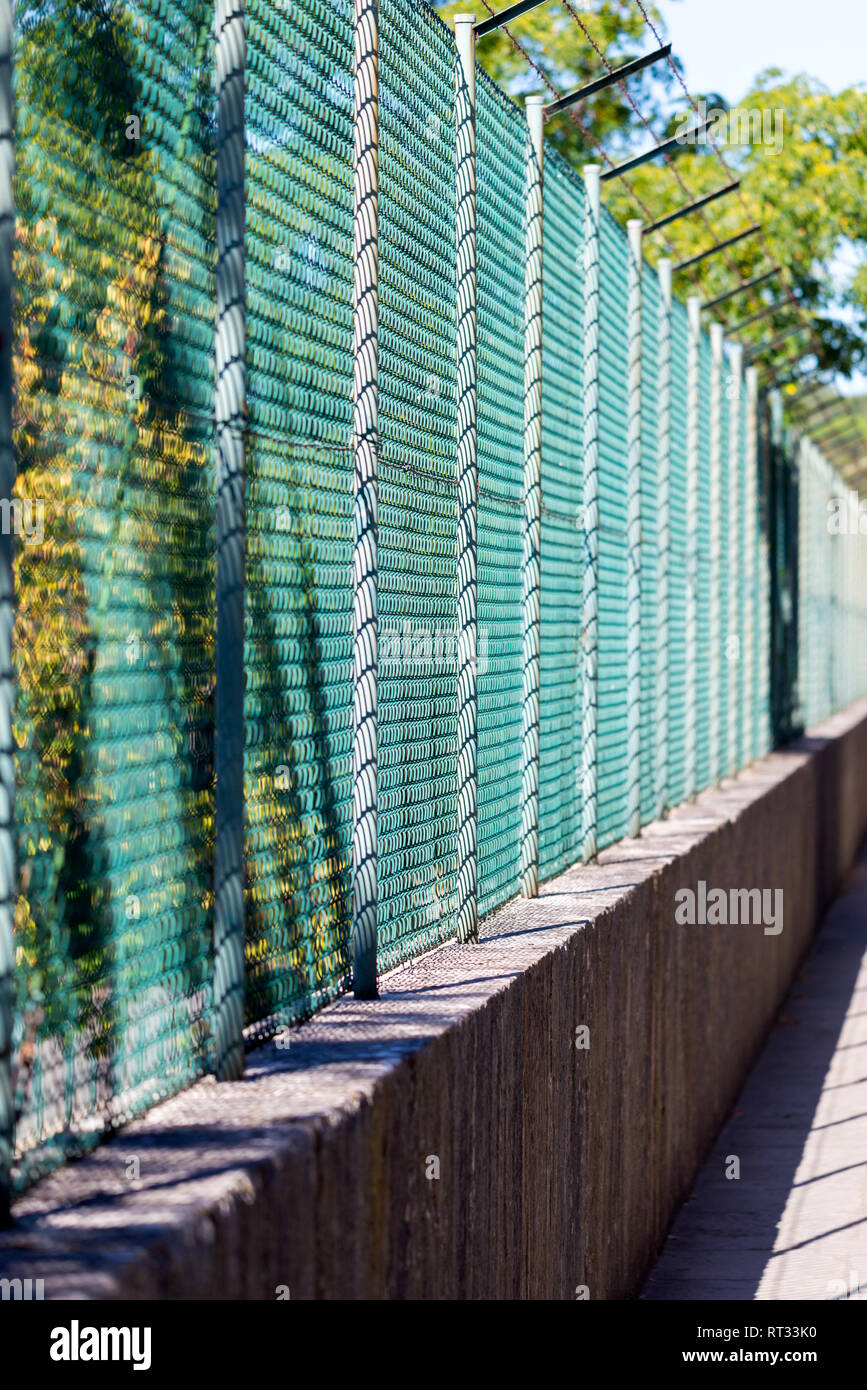 Wire mesh fence and a restricted area sign with blue sky background. - Stock Image