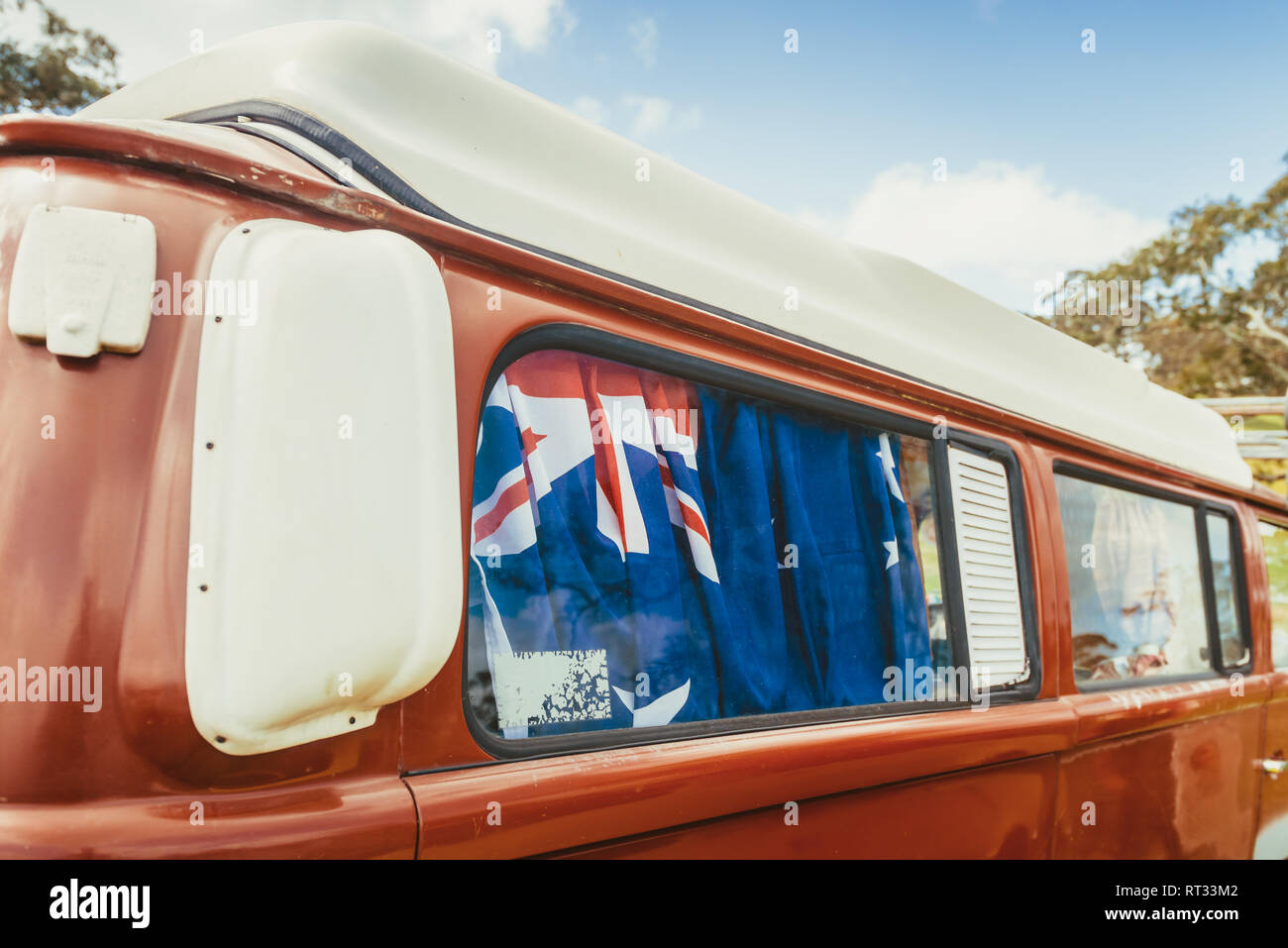 Old australian camper van with flag of Australia behind its rear window parked in caravan park on a day - Stock Image