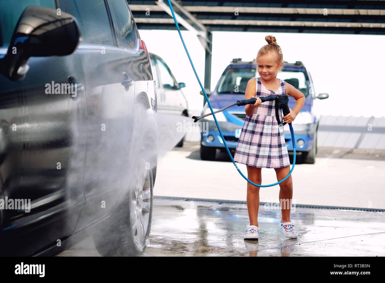 Lovely little preschool girl in summer dress helping to