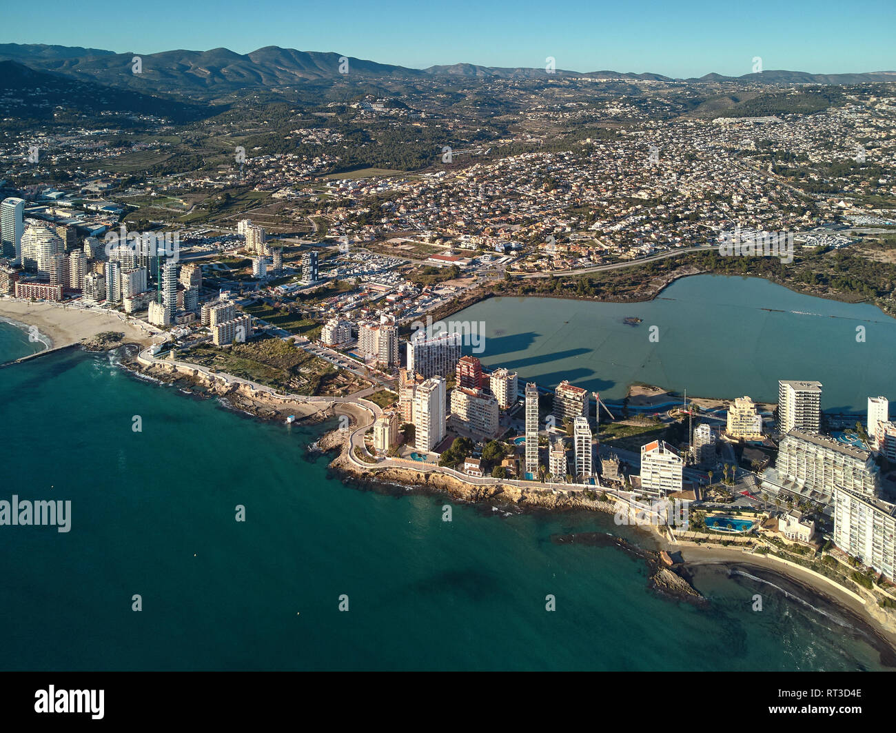 Drone point of view Calpe spit between Mediterranean Sea and lake. Cityscape modern skyscrapers sunny day green turquoise water, comarca of Marina Alt - Stock Image