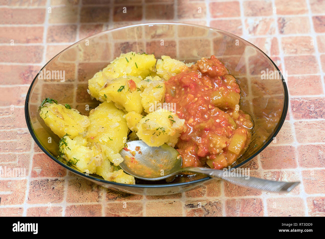 Potatoes with vegetables in a plate with a spoon on table - Stock Image