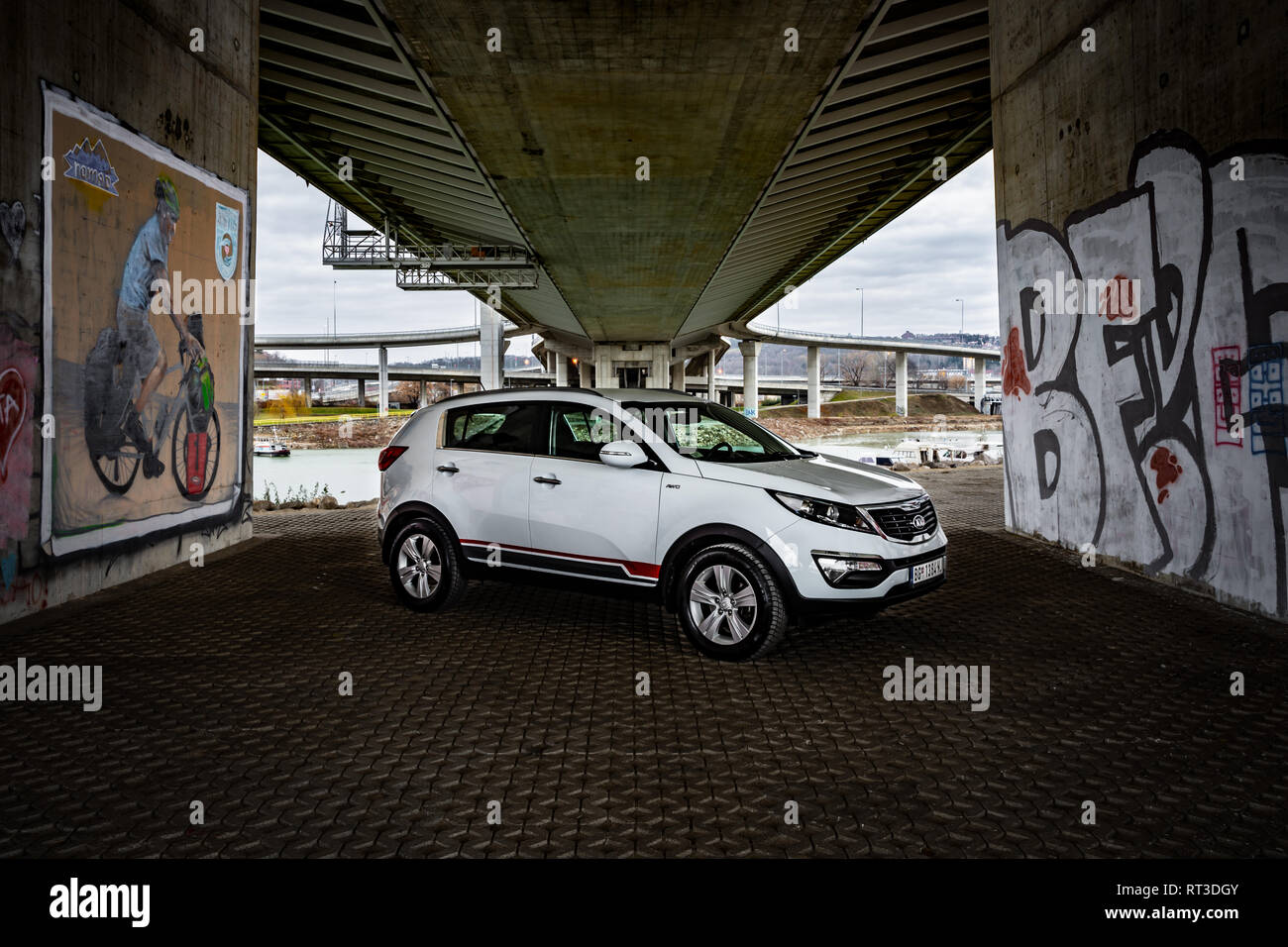 SUV Kia Sportage 2.0 CRDI awd or 4x4, white color, parked under the bridge, on the banks of the river Sava. Stock Photo