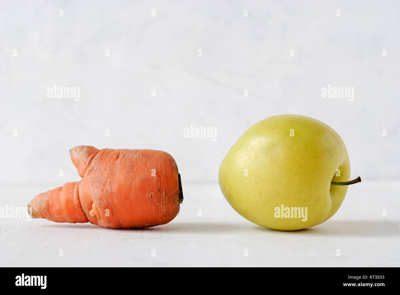 Misshapen ugly fresh golden apple and carrot with appendages on white viewed low angle close up - Stock Image