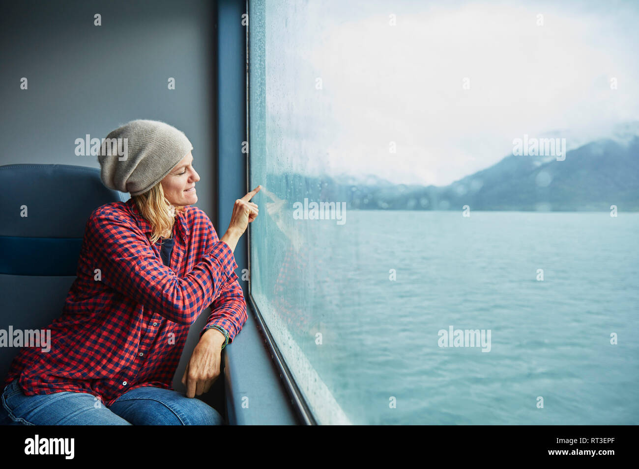 Chile, Hornopiren, woman drawing a heart on the window of a ferry Stock Photo