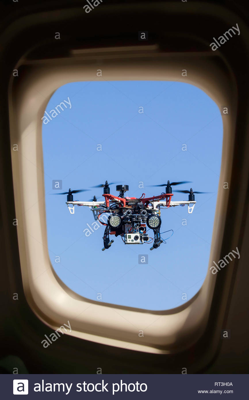 Concept of drone flying dangerously too close to a commercial aircraft. This is a combination of two images. - Stock Image