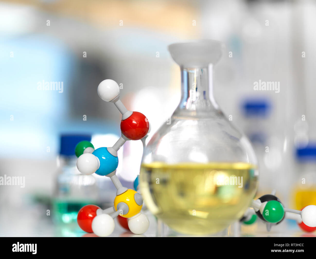 Flask containing a chemical formula next to molecule model - Stock Image