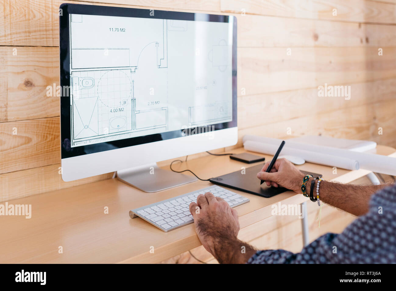 Close-up of man working on floor plan at home using the computer and graphics tablet - Stock Image