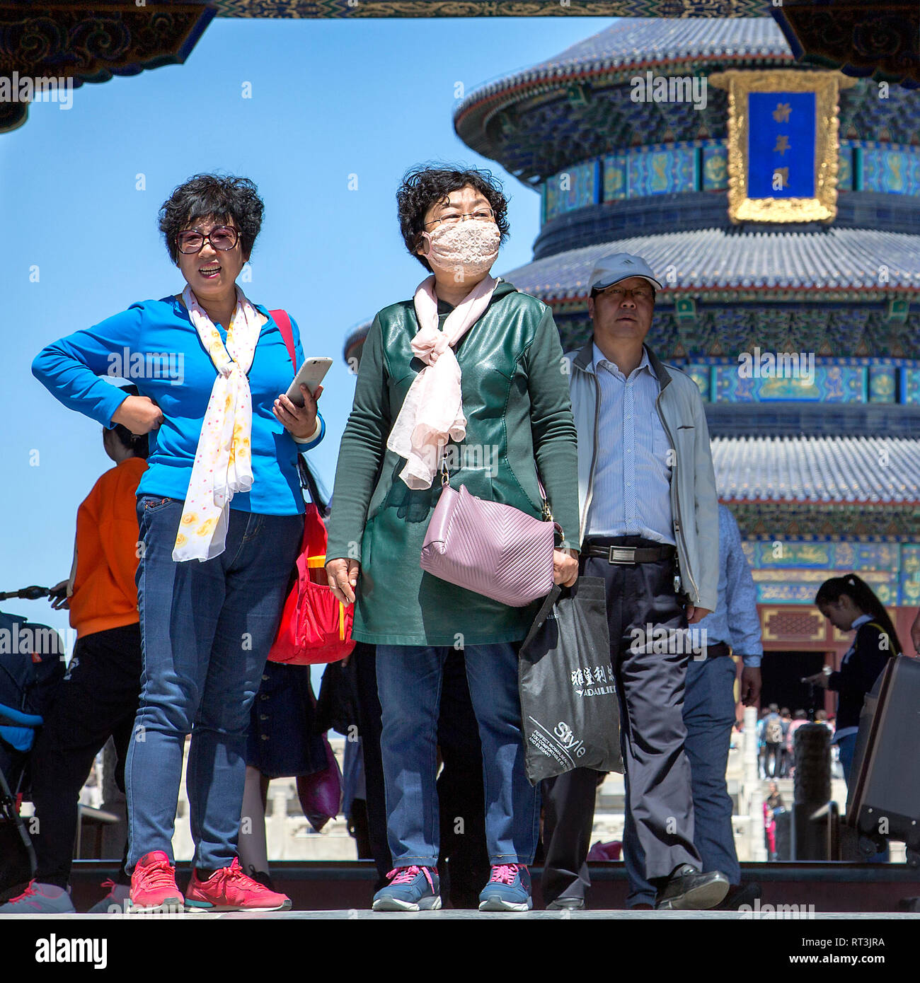 Two female tourists stand in The Temple of Heaven complex, one wears a pollution mask. Behind them The Hall of Prayer for Good Harvests can be seen. - Stock Image