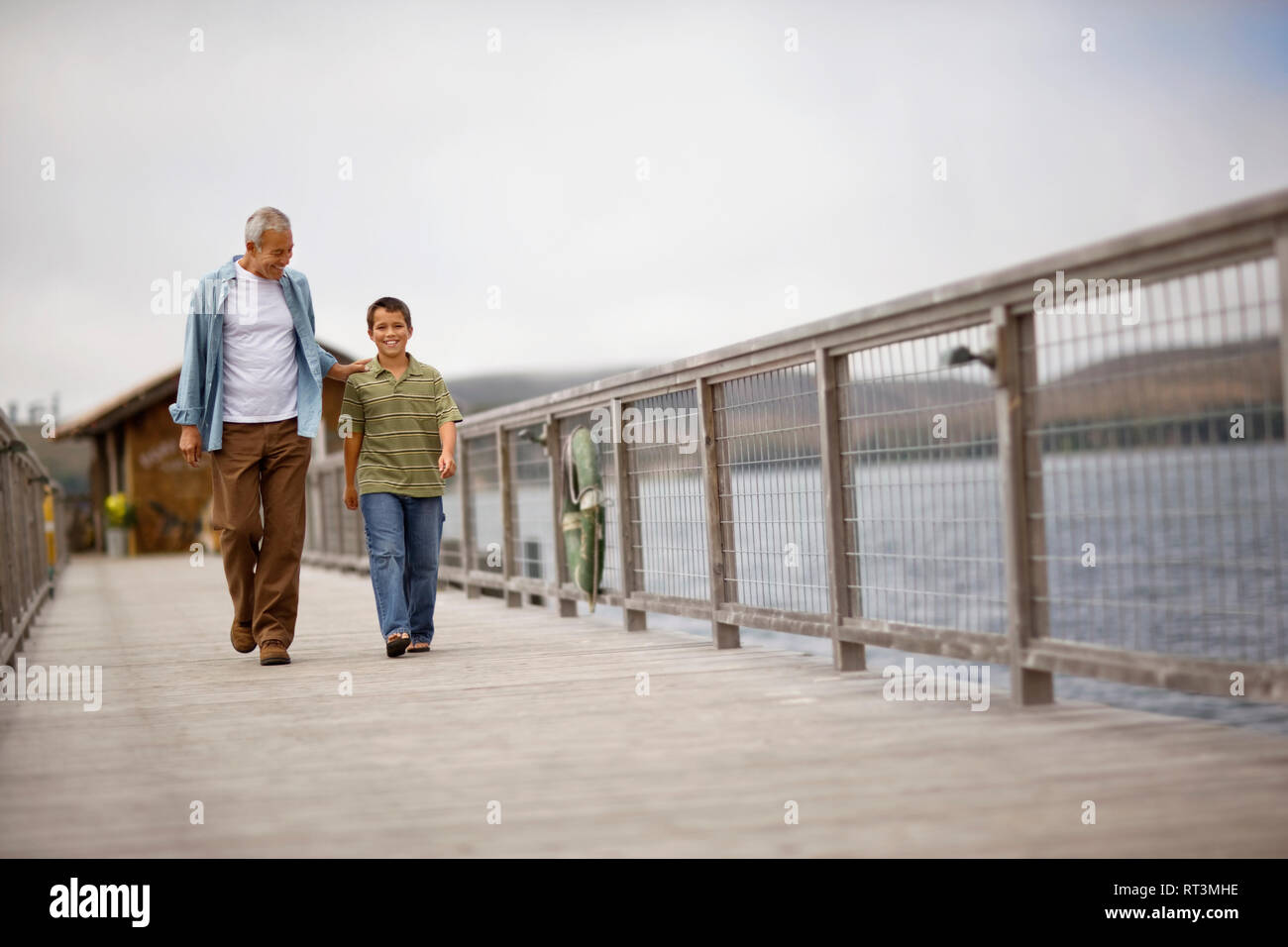 Portrait of a young boy walking along a pier with his mature grandfather. Stock Photo