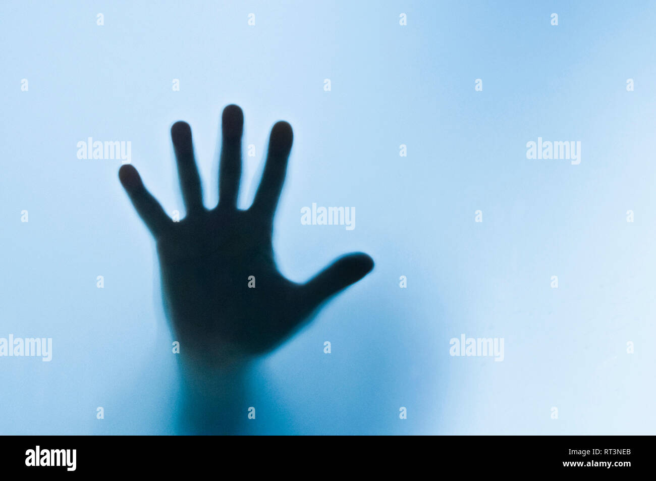 silhouette of the hand of a person behind a glass - image for book cover - Stock Image