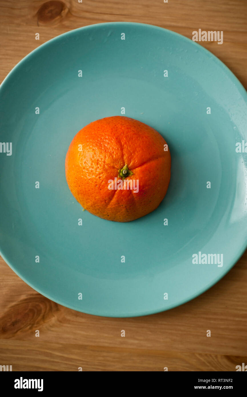 half orange fruit on a aquamarine blue plate Stock Photo
