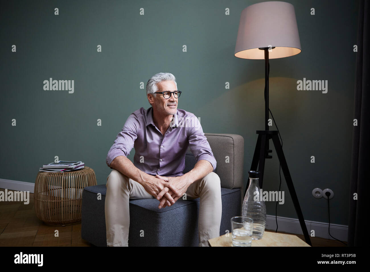 Mature man sitting on armchair at home - Stock Image
