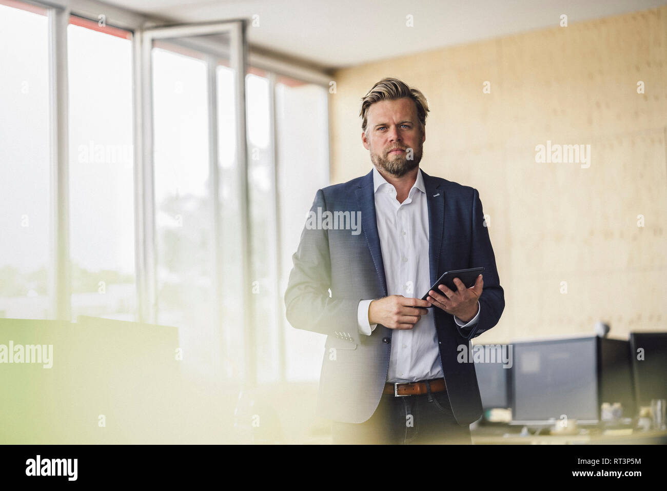Businessman standing in office, using digital talet - Stock Image