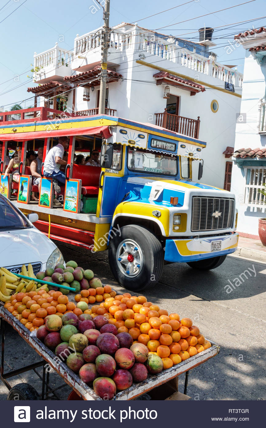 Cartagena Colombia Old Walled City Center centre Getsemani traditional neighborhood street fruit vendor mangoes oranges chiva painted sightseeing bus - Stock Image