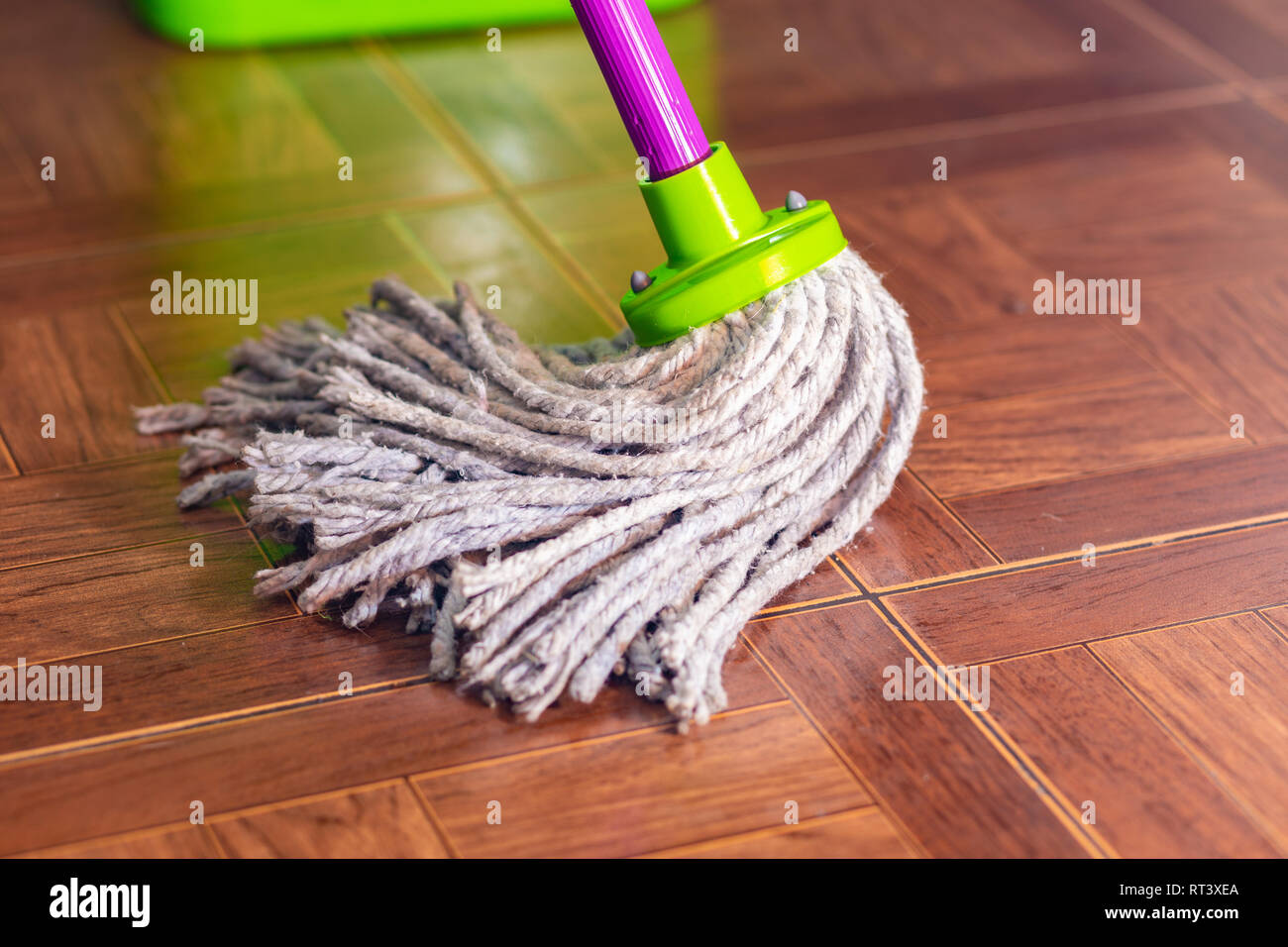 Rope mop wipes the floor of the tile. - Stock Image
