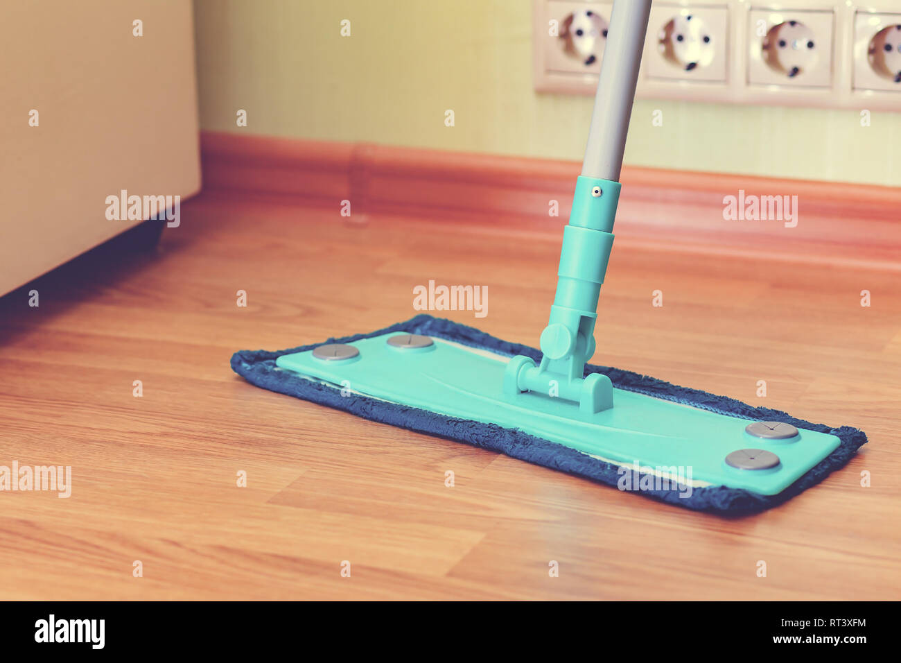 Blue mop on the floor of brown laminate - Stock Image
