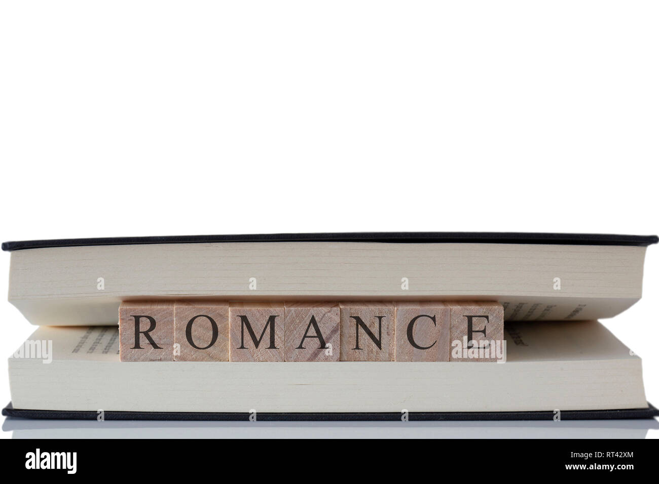 Romance written on wooden blocks inside a book isolated on a white background with reflection Stock Photo
