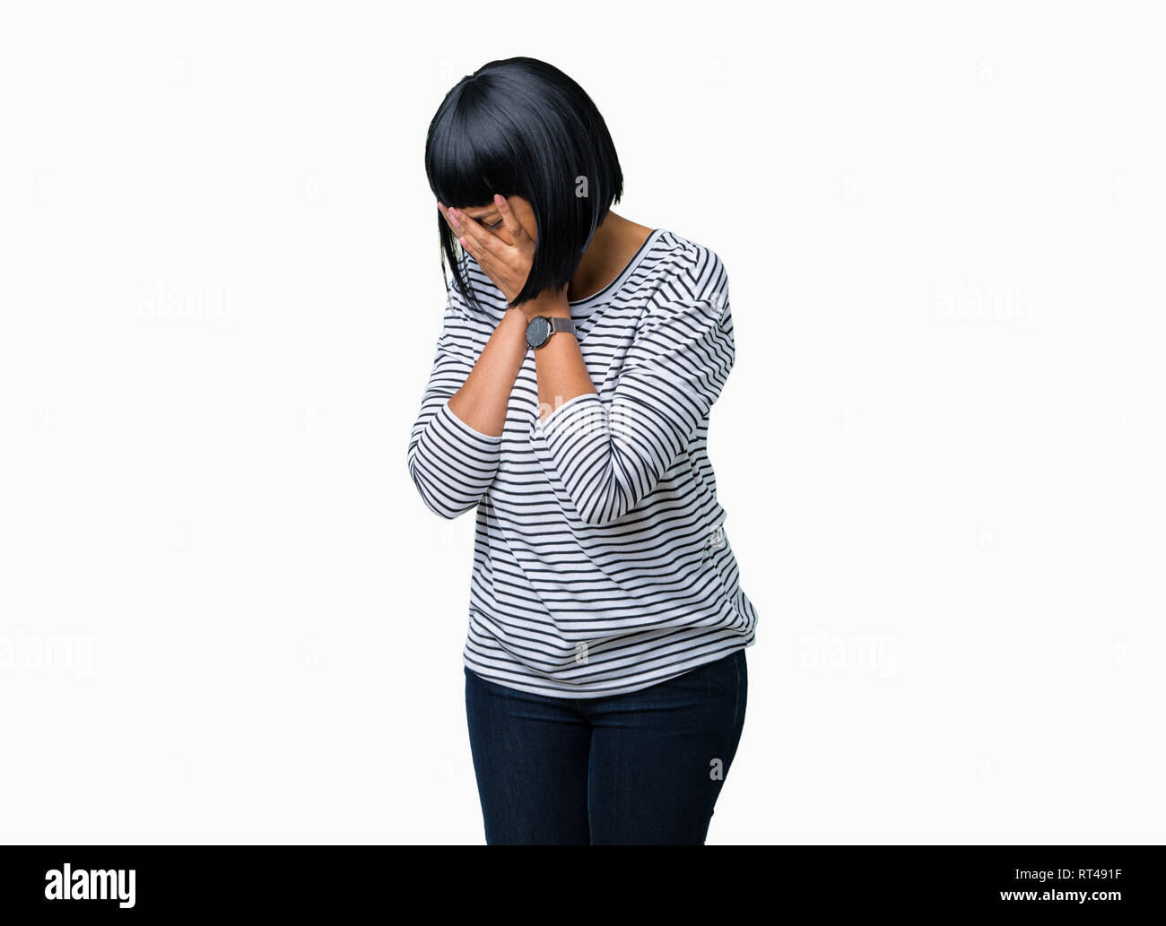 Beautiful young african american woman wearing stripes sweater over isolated background with sad expression covering face with hands while crying. Dep - Stock Image