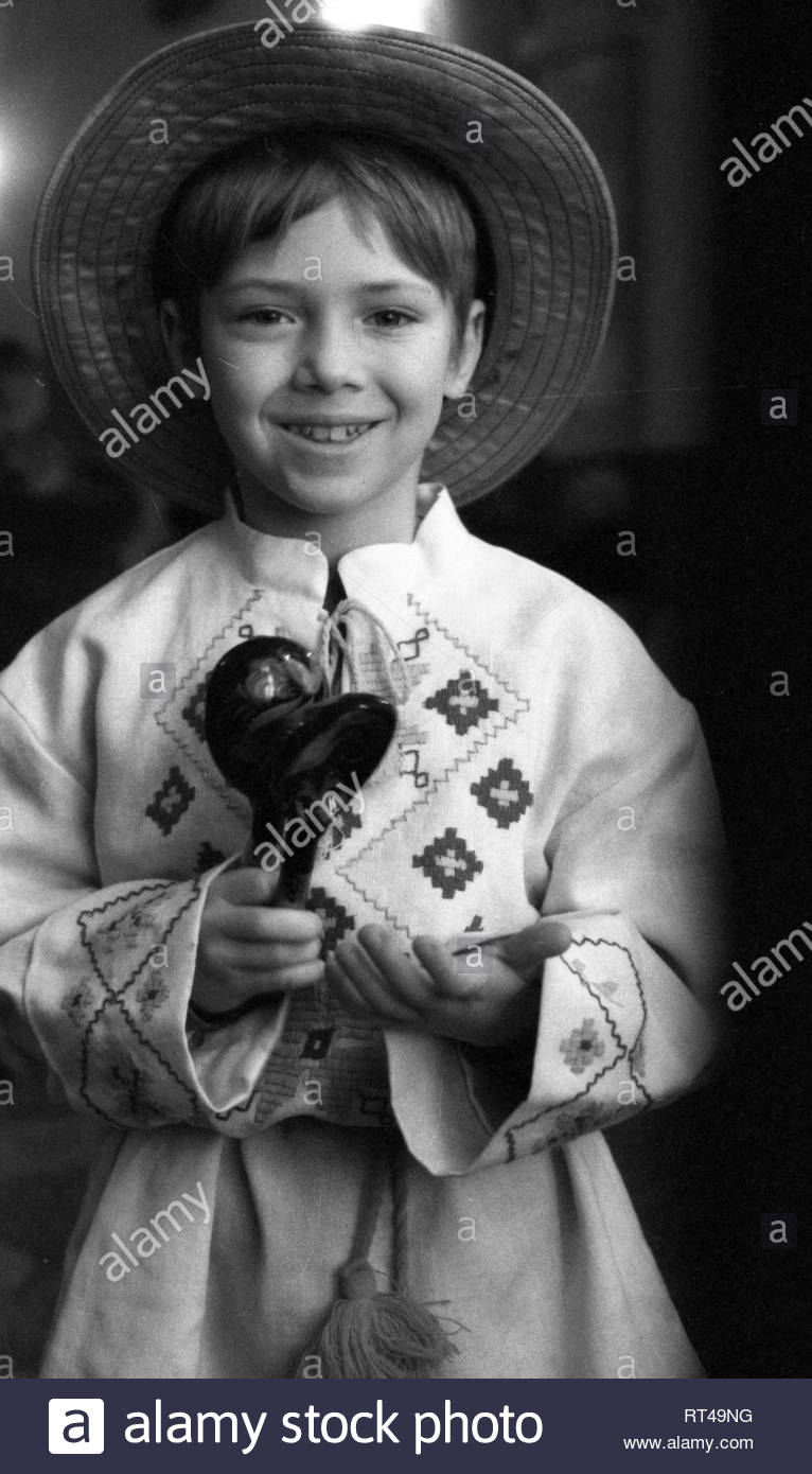 This is a portrait of Belarusian boy in national dress. The talented child is a member of an Amateur team of folk art, where he played on wooden spoons. The child is wearing a straw hat. The Belarusian national ornament is embroidered on a long linen shirt. The shirt is tied with threads of linen. In the hands of the artist is wooden spoons. - Stock Image