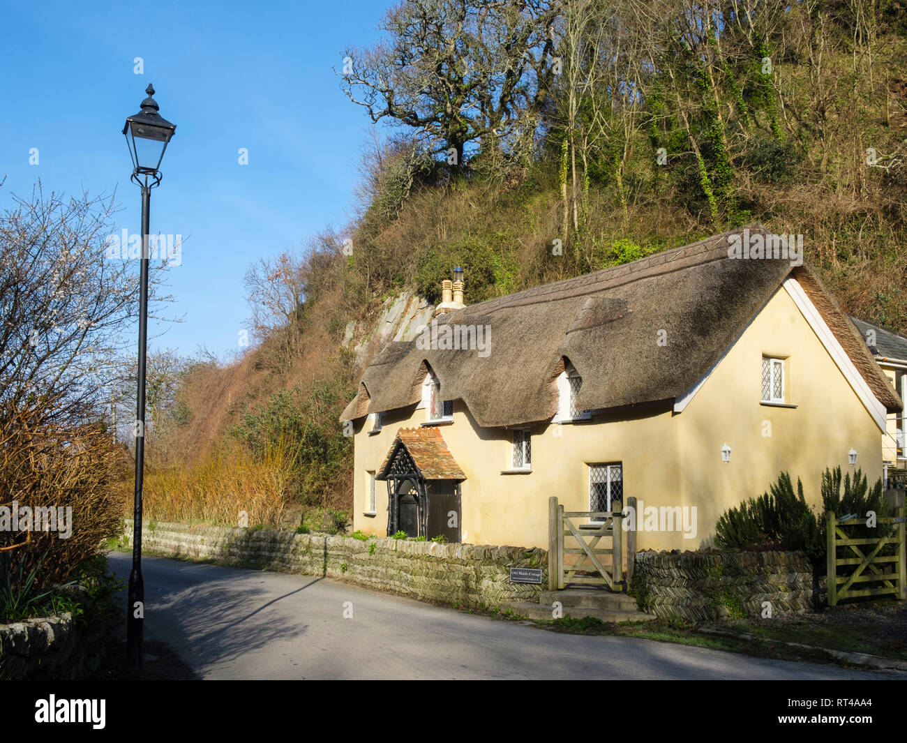 17th century Old Maids Cottage 1653 with a traditional thatched roof in pretty English country village of Lee, North Devon, England, UK, Britain - Stock Image