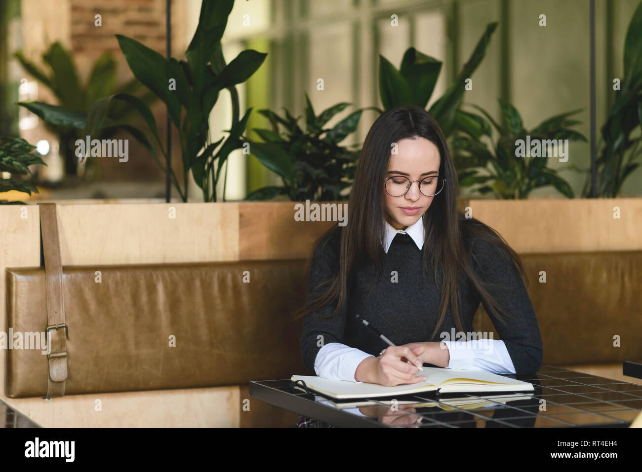 Brunette girl in eyewear writting home tasks in the notebook whilee sitting at the cafe - Stock Image